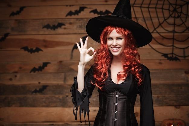 Concept de sorcière halloween - happy halloween cheveux rouges sorcière tenant le signe ok avec les doigts posant sur fond de studio en bois ancien.