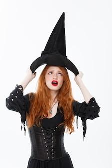 Concept de sorcière d'halloween - happy halloween cheveux roux sexy sorcière se battant avec son chapeau magique volant au-dessus de sa tête. isolé sur mur blanc.