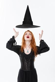 Concept de sorcière d'halloween - happy halloween sorcière sexy aux cheveux roux avec un chapeau magique volant au-dessus de sa tête. isolé sur mur blanc.