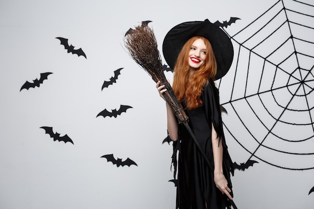 Concept de sorcière d'halloween portrait de la belle jeune sorcière avec manche à balai sur mur gris avec mur de chauve-souris et toile d'araignée