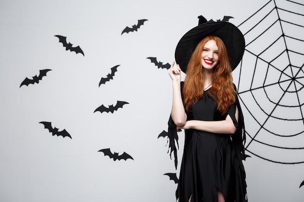 Concept de sorcière d'halloween sorcière d'halloween heureuse tenant posant sur un mur gris foncé avec une chauve-souris et une toile d'araignée