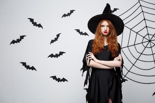 Concept de sorcière d'halloween sorcière d'halloween tenant posant avec une expression sérieuse sur un mur gris foncé avec une chauve-souris et une toile d'araignée