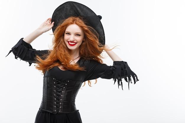 Concept de sorcière d'halloween - sorcière heureuse de cheveux de gingembre d'halloween. isolé sur mur blanc.