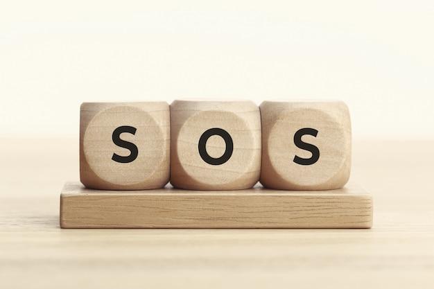 Concept sos. bloc en bois avec texte sur table.