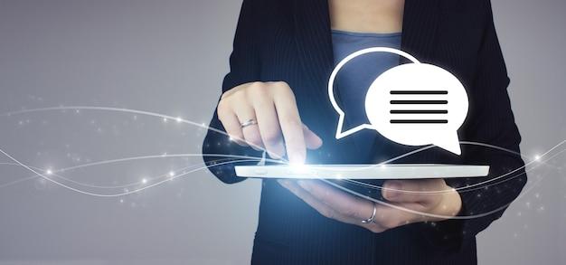 Concept de soutien aux entreprises. questions en ligne. tablette blanche en main de femme d'affaires avec hologramme numérique faq question réponse signe sur fond gris. concept de faq, quoi où quand comment et pourquoi.