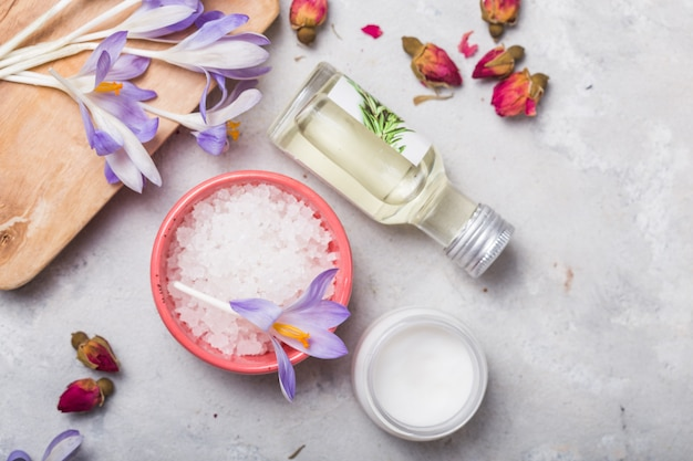 Concept de spa et de bien-être avec du sel de mer, des roses sèches, une brosse, de l'huile et une serviette sur fond gris, bannière, espace copie, vue de dessus