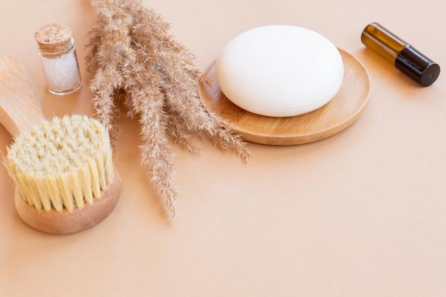 Concept de spa et de bien-être avec sel de mer, pampa sèche, brosse pour le visage, huile essentielle et barre de savon sur fond beige, espace de copie. accessoires de soins du visage bio respectueux de l'environnement.