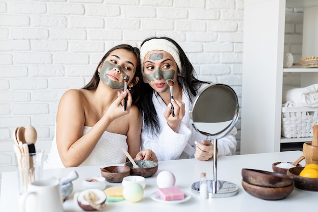 Concept de spa et de bien-être. soins auto-administrés. deux belles femmes appliquant un masque facial s'amusant