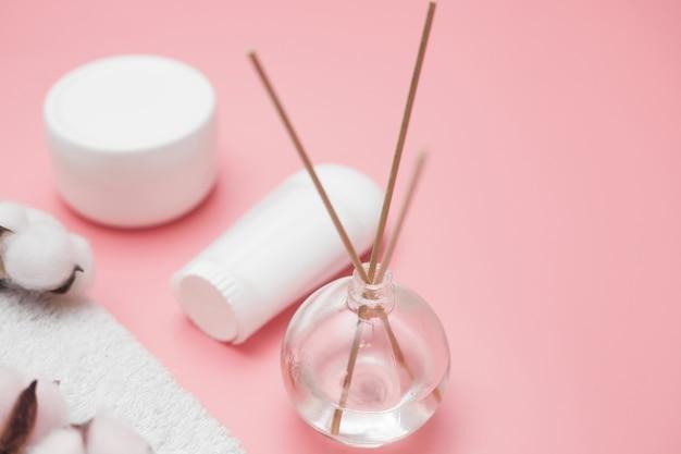 Concept de spa, bocaux en coton blanc sur fond rose, espace copie, vue de dessus. photo de haute qualité