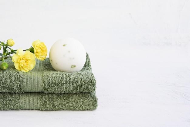 Concept de spa. bombe de bain blanche et deux serviettes vertes décorées de fleurs d'oeillets jaunes sur blanc