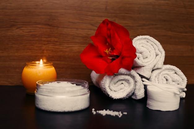 Concept de spa. bougie allumée, serviettes blanches, fleurs et sel. fond sombre.