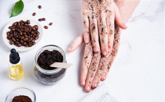 Concept de spa. une jeune femme fait un massage des mains avec un gommage au café fait maison