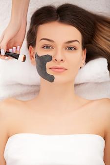 Concept de spa. jeune femme avec masque facial nutritif dans un salon de beauté, close up
