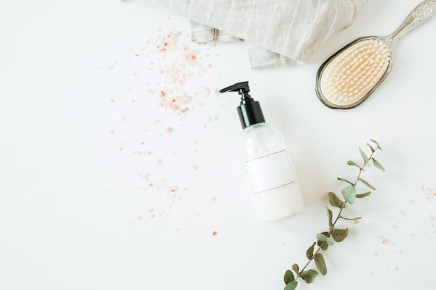 Concept de spa de soins de santé avec bouteille de savon liquide copie espace, eucalyptus, brosse à cheveux sur blanc