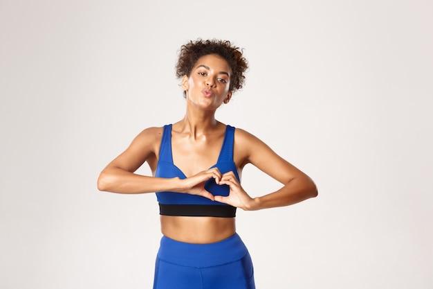 Concept de sport et d'entraînement.belle femme jeune et saine de remise en forme en tenue de gym bleue, montrant