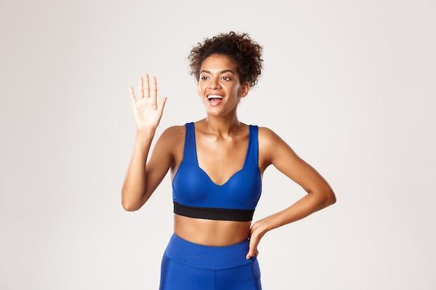 Concept de sport et d'entraînement. femme fitness afro-américaine amicale disant bonjour, agitant la main et