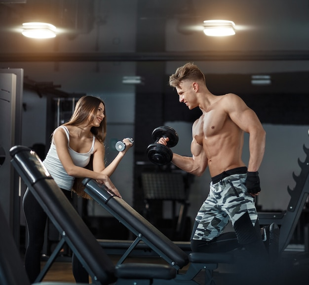 Concept de sport, d'entraînement, de remise en forme, de style de vie et de personnes - jeune femme avec un entraîneur personnel fléchissant le dos et les muscles abdominaux sur un banc dans une salle de sport. photo de haute qualité