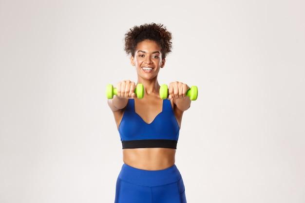Concept de sport et d'entraînement. sourire jolie femme de remise en forme en vêtements de gym bleu, levage