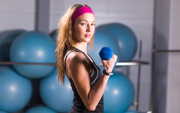 Concept de sport, fitness, formation et bonheur - mains de femme sportive avec des haltères bleu clair.