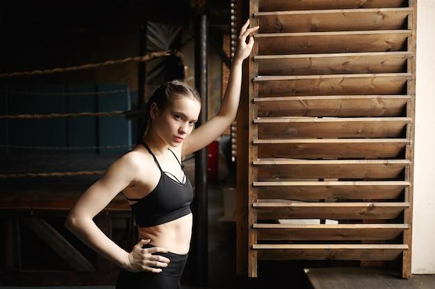 Concept de sport, fitness, style et mode. confiant séduisante jeune sportive avec bras musclés posant à la fenêtre, s'appuyant sur un volet en bois