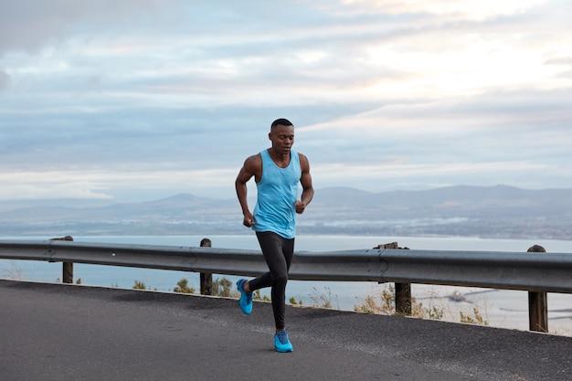 Concept de sport, de motivation et de loisirs. le jogger noir sportif masculin actif court contre le ciel sans nuages sur l'autoroute, porte un gilet décontracté et des chaussures de sport bleues, a des biceps sur les bras, des exercices en plein air.