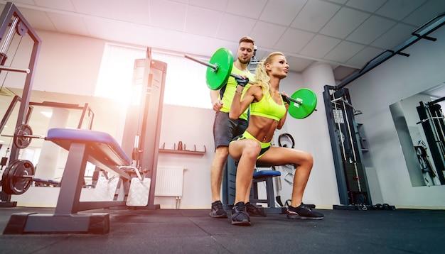 Concept de sport, musculation, style de vie et personnes - jeune homme et femme avec haltères flexion des muscles et faisant squat presse épaule dans la salle de gym.