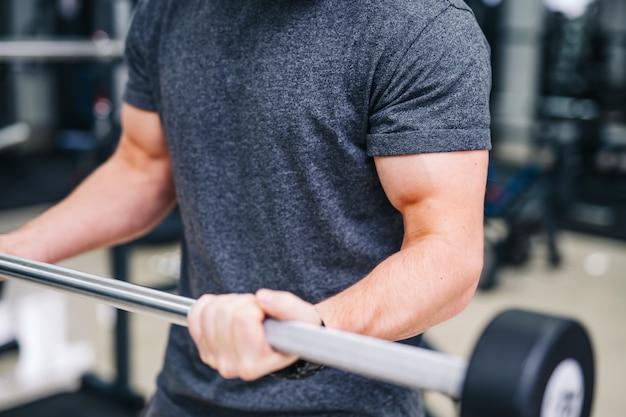 Concept de sport, musculation, style de vie et personnes - jeune homme soulevant des haltères et flexion des muscles agrandi. mains d'homme fort au gymnase.