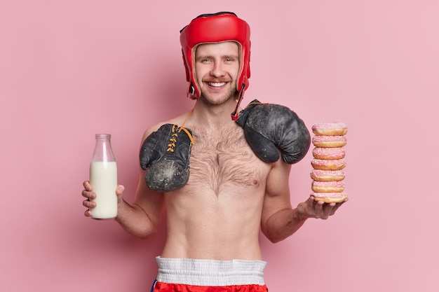 Concept de sport et de nutrition des gens. un boxeur masculin maigre positif pose avec des sourires de torse nu a volontiers la tentation de manger des beignets et de boire du lait