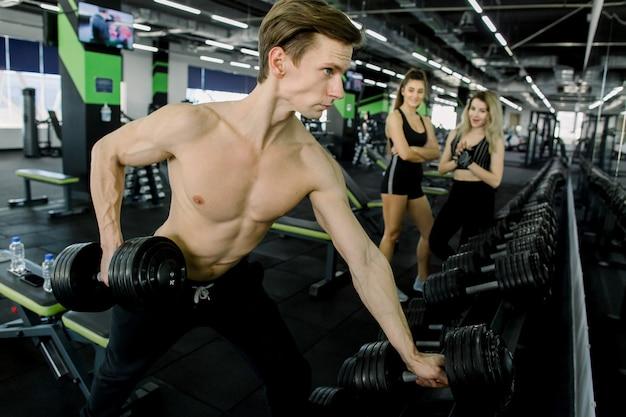 Concept de sport, de remise en forme, de style de vie et de personnes - entraîneur de fitness pour jeunes hommes, flexion des muscles avec des haltères en salle de gym deux jeunes filles regardant en arrière-plan
