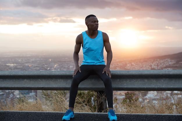 Concept de sport tôt le matin. un homme ethnique noir réfléchi est assis au panneau de signalisation, pose contre une vue magnifique sur le lever du soleil, bénéficie d'une atmosphère calme, porte une veste bleue, un pantalon noir et des chaussures de sport.
