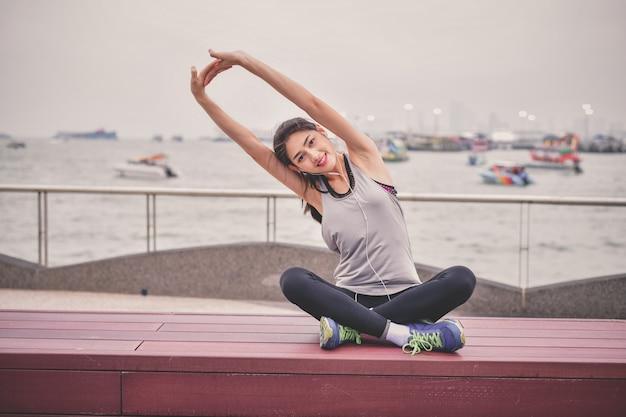 Concept sportif. belle fille exerce sur la plage avec échauffement.