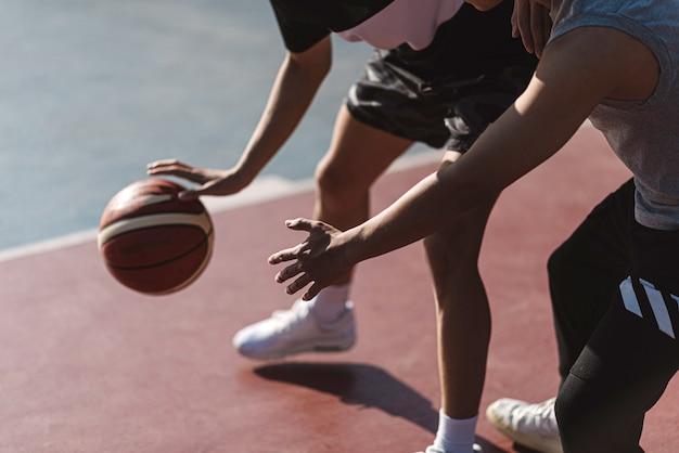 Concept de sports et de loisirs deux joueurs de basket-ball masculins appréciant jouer au basket-ball ensemble sur le terrain de sport.