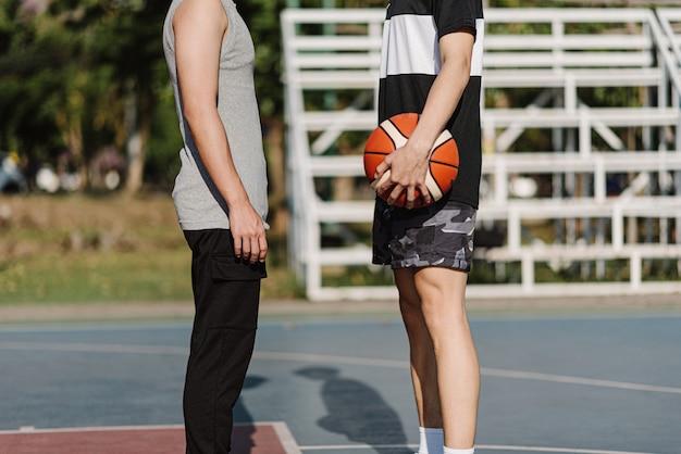 Concept de sports et de loisirs, deux joueurs opposés se font face avant le début du match de basket-ball.