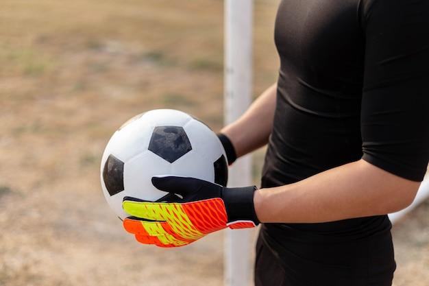 Concept de sports et de loisirs un gardien de but adolescent portant une tenue noire et une paire de gants colorés tenant un ballon de football.