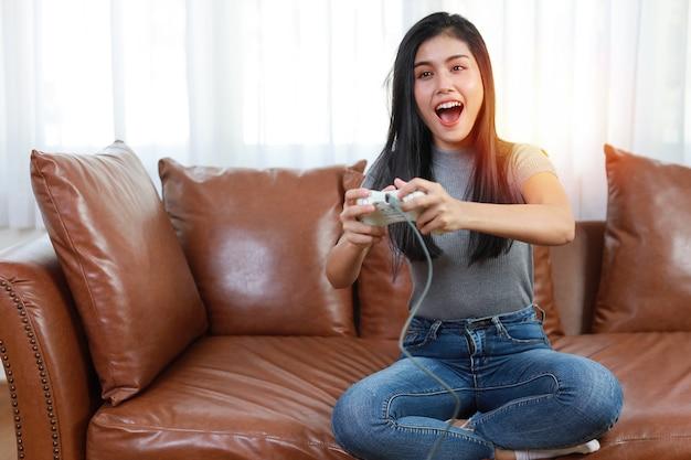 Concept de station de console de jeu vdo. femme asiatique active assise sur un canapé, tenant un joystick et jouant à un jeu passionnant. jolie fille avait l'air excitée avec la console du contrôleur de jeu
