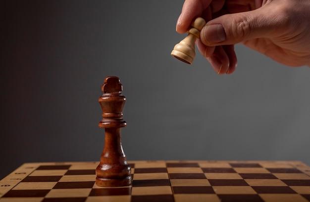 Concept de stratégie d'entreprise. pion faisant la dernière étape finale pour faire échec et mat aux échecs.