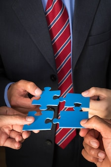 Concept de stratégie d'équipe commerciale. hommes avec des pièces de puzzle