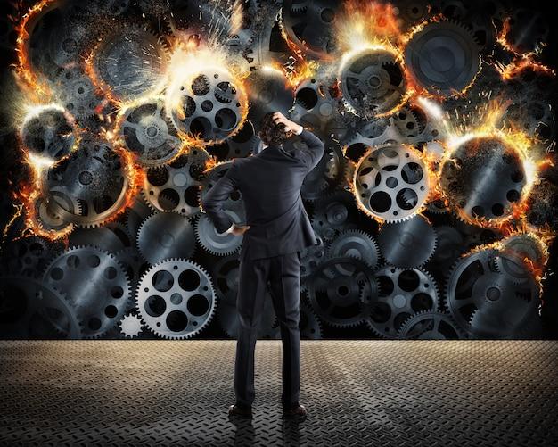 Concept de stress avec un homme d'affaires surmené regarde désespérément un mécanisme d'engrenage brûler