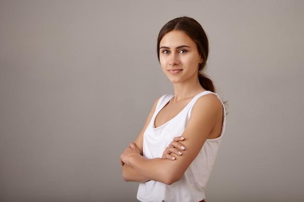 Concept de style, de confiance et de personnes. coup de taille de jolie jeune femme en haut blanc décontracté croisant les bras sur sa poitrine étant de bonne humeur, avec un sourire confiant positif