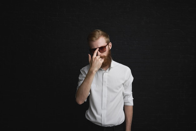 Concept de style et de mode. beau jeune homme à la mode avec barbe au gingembre posant en tenue de soirée, ajustant des lunettes de soleil élégantes, ayant une expression confiante