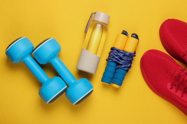 Concept de style plat laïc de mode de vie sain, de sport et de remise en forme. chaussures de sport pour la course, haltères, bouteille d'eau, corde à sauter sur fond jaune. vue de dessus
