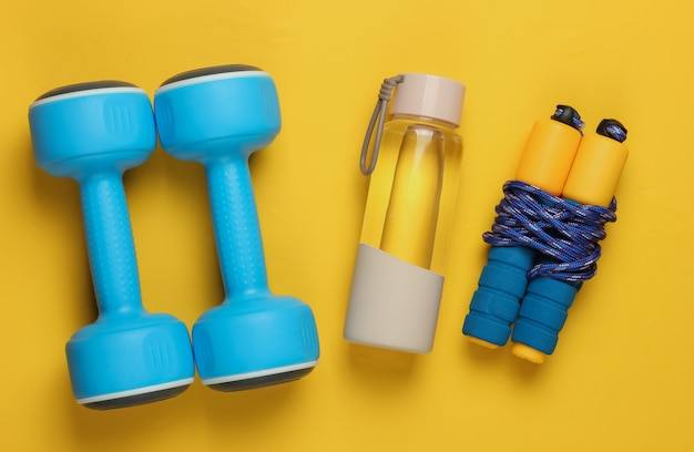 Concept de style plat laïc de mode de vie sain, de sport et de remise en forme. haltères, bouteille d'eau, corde à sauter sur fond jaune. vue de dessus
