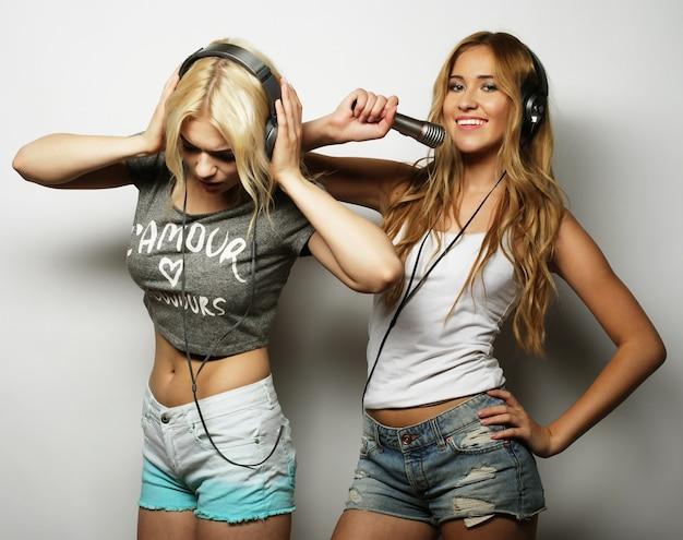 Concept de style de vie, de bonheur, d'émotion et de personnes : filles hipster de beauté avec un microphone chantant et s'amusant