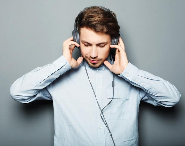 Concept de style de vie, de bonheur, d'émotion et de personnes: profiter de sa musique préférée. heureux jeune homme élégant ajustant son casque ad souriant en se tenant debout contre l'espace gris