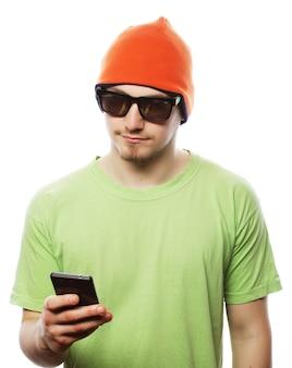 Concept de style de vie, de technologie et de personnes : homme gai en chemise verte et chapeau lumineux utilisant un smartphone, isolé sur blanc