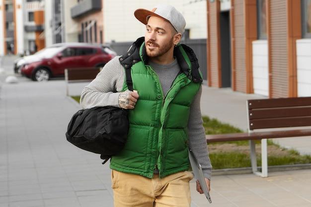 Concept de style de vie urbain, de technologie et de voyage. séduisant jeune homme européen à la mode avec chaume portant des vêtements élégants, portant un sac à bandoulière noir et une tablette numérique, partant en voyage d'affaires