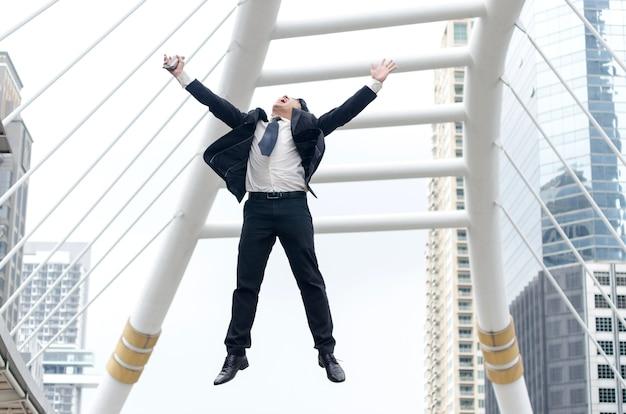 Concept de succès. homme d'affaires asiatique sautant avec un moment heureux.