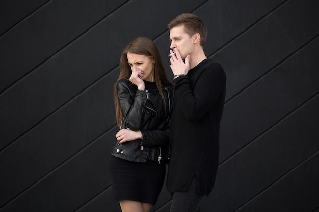 Concept de tabagisme passif la femme se couvre le visage de la fumée de cigarette