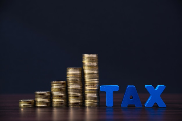 Concept de taxe. alphabet fiscal avec pile de pièce de monnaie en fond sombre, concept commercial et financier.