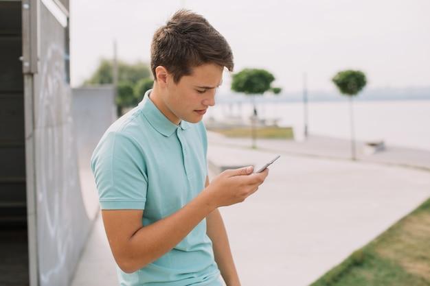 Concept de technologie, internet et personnes - adolescent heureux avec smartphone à l'extérieur.